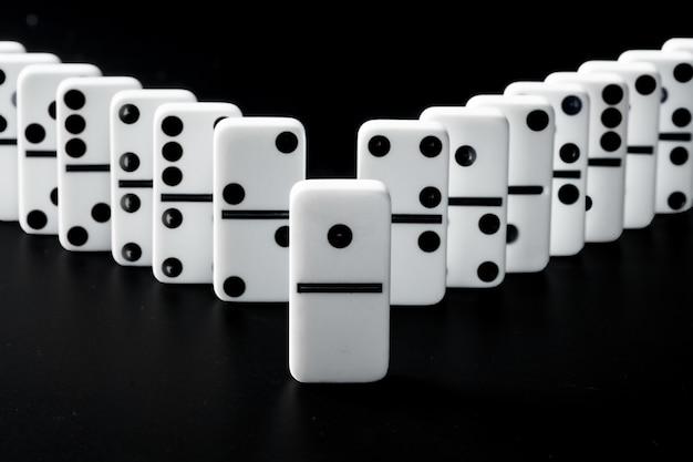 Piezas de dominó en fila sobre superficie negra