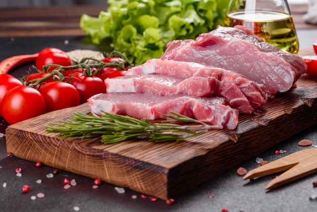 Piezas frescas de cerdo listo para cocinar en la cocina. medallones de solomillo filetes en una fila listos para cocinar