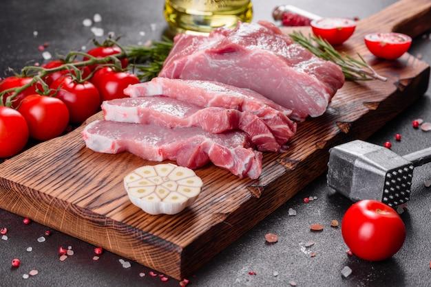 Piezas frescas de cerdo listo para cocinar. medallones de solomillo filetes en una fila listos para cocinar