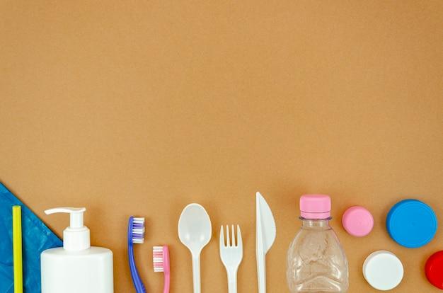 Piezas de plástico reciclables sobre fondo marrón.