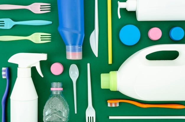 Piezas de plástico reciclables sobre fondo verde.