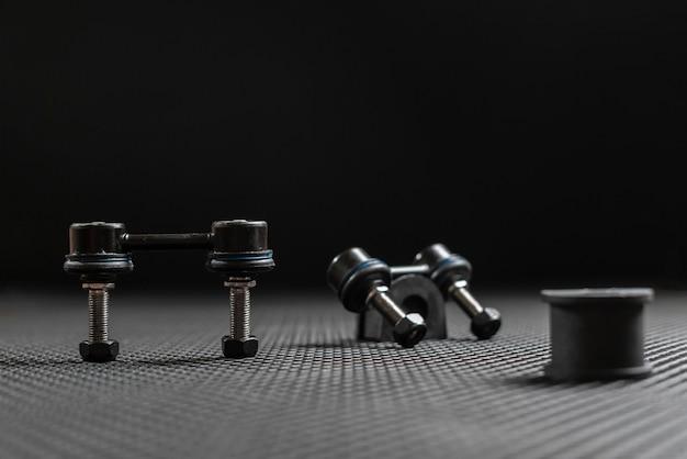 Piezas de repuesto de un coche nuevo, brazos de detalles de suspensión aislados sobre fondo oscuro plano