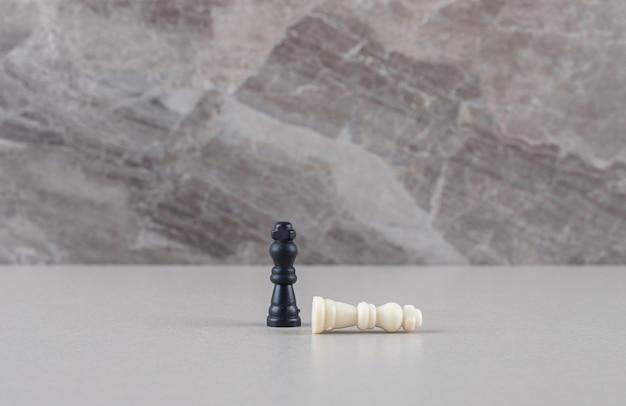 Piezas de rey de ajedrez blanco y negro sobre mármol