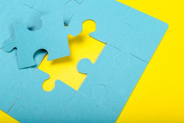 Piezas de un rompecabezas azul sobre amarillo