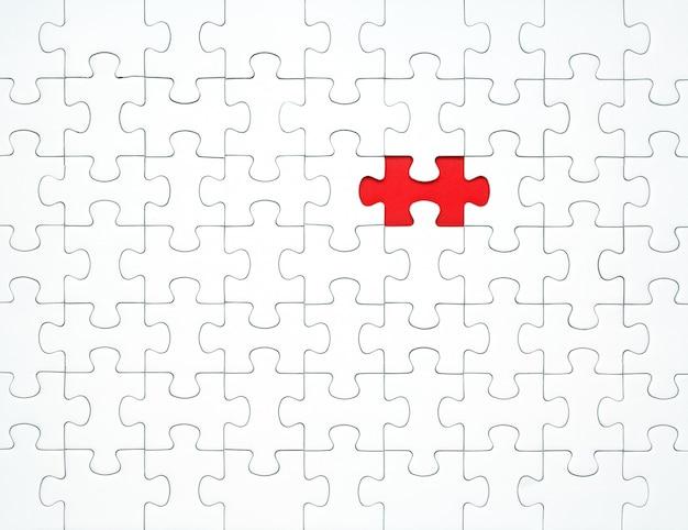 Piezas de un rompecabezas blanco sobre un fondo rojo separados