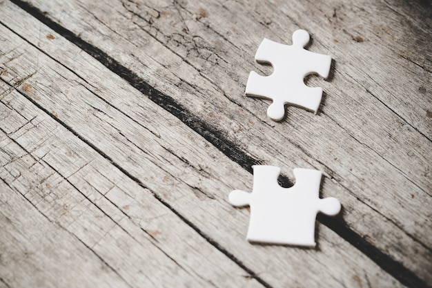 Piezas de rompecabezas blanco sobre madera