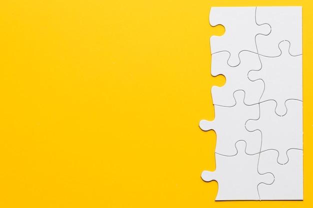 Piezas de rompecabezas blanco sin terminar sobre fondo amarillo