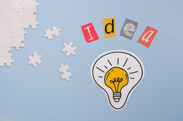 Piezas de rompecabezas y letras de ideas con bombilla