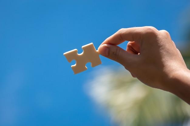 Piezas de rompecabezas en manos de la mujer con fondo de cielo azul