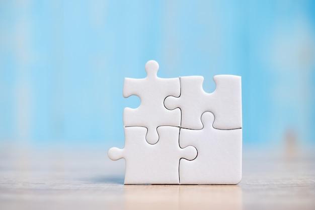Piezas del rompecabezas sobre fondo de mesa de madera. soluciones comerciales, objetivo de misión, éxito, objetivos, cooperación, asociación y estrategia.