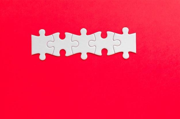 Piezas del rompecabezas sobre fondo rojo. conocimiento de los negocios.