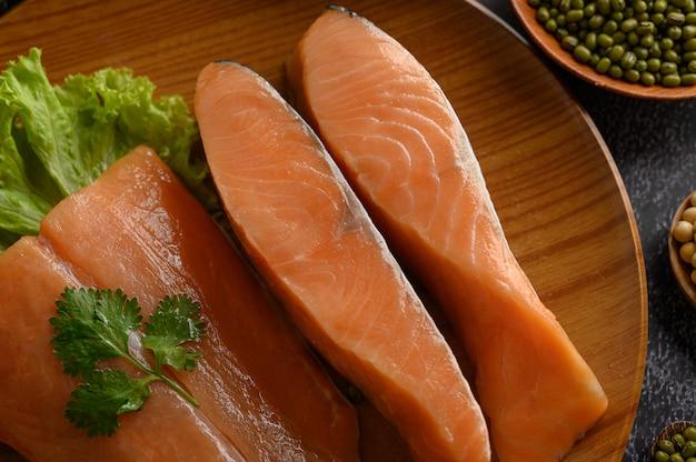 Piezas de salmón en un plato de madera. enfoque selectivo