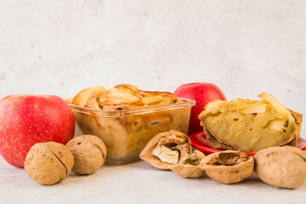 Piezas de tarta de manzana en la mesa con nueces