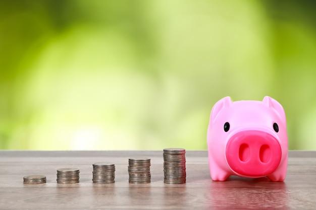 Piggy con pila de monedas en la mesa de madera
