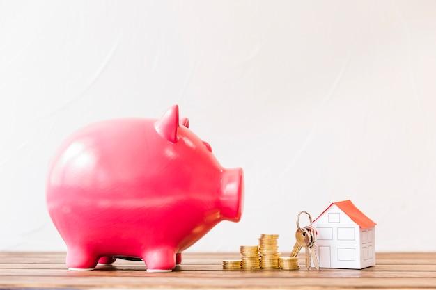 Piggybank cerca de monedas apiladas y casa con llave