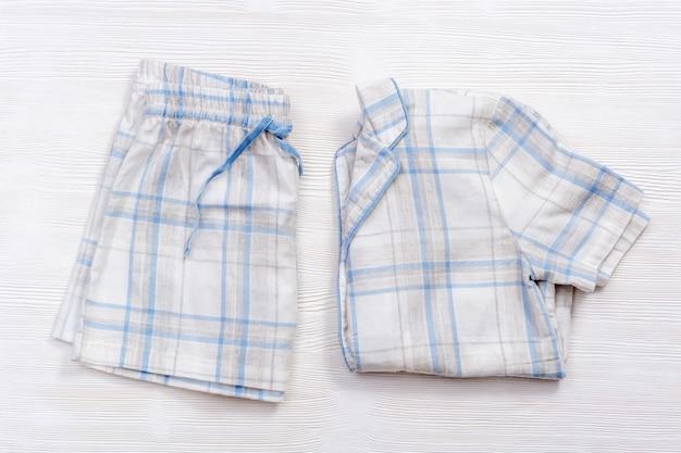 Pijama blanco cálido doblado con cuadros o rayas azules en madera blanca