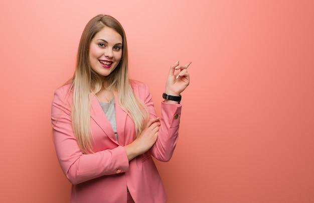 Pijama que lleva de la mujer rusa joven que señala al lado con el finger