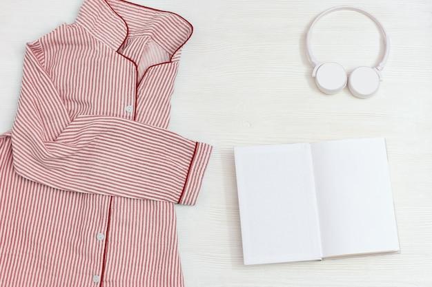 Pijama rosa para niñas, auriculares y libro abierto, ropa de dormir cómoda para un sueño tranquilo.
