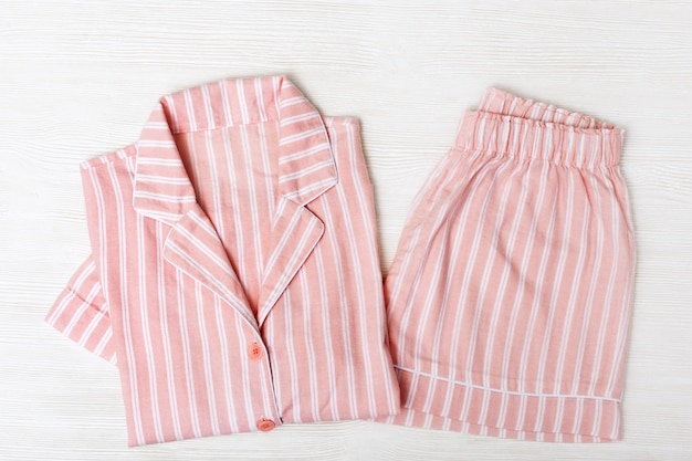 Pijama rosa sobre superficie de madera blanca.