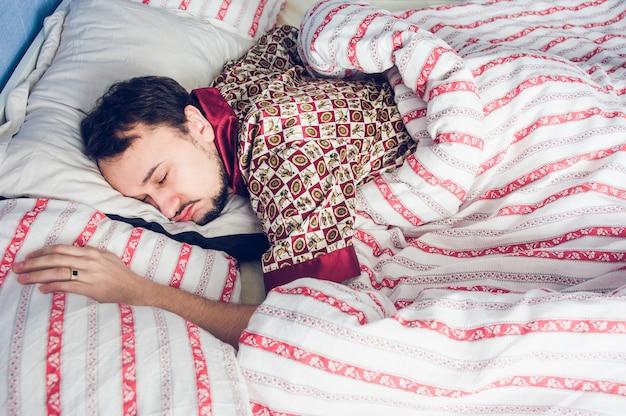 Pijamas de hombre dormidos en la cama.