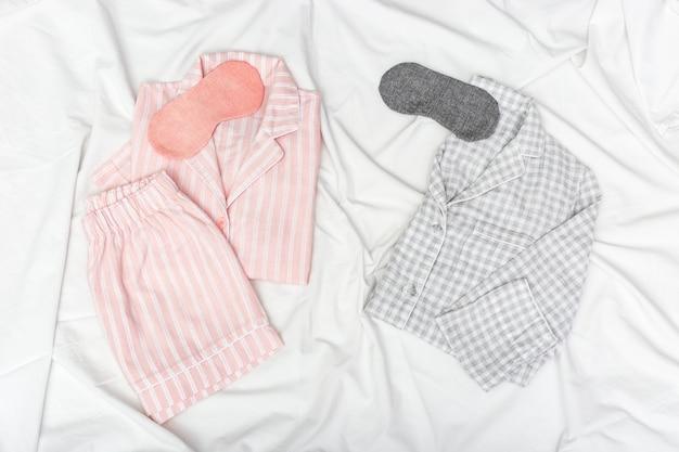 Pijamas rosas y grises para dos personas, y máscara para dormir para los ojos en sábanas de algodón blanco.