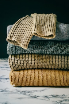 Pila de acogedores suéteres de punto. concepto otoño-invierno, suéteres de lana de punto. montón de ropa de invierno tejida, suéteres, prendas de punto