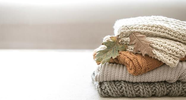Pila de artículos tejidos cálidos del armario de otoño de cerca en el espacio en blanco borrosa copia espacio.