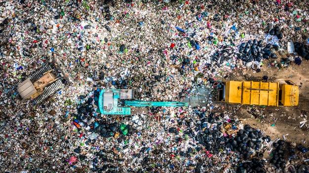 La pila de basura en un basurero o vertedero, los camiones de basura de vista aérea descargan la basura en un vertedero, el calentamiento global.