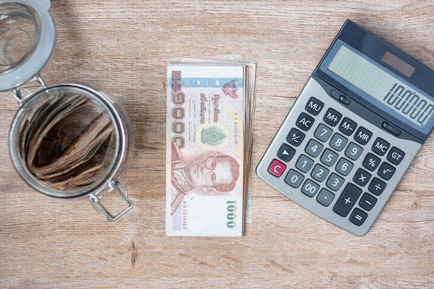 Pila de billetes de baht tailandés y con calculadora.
