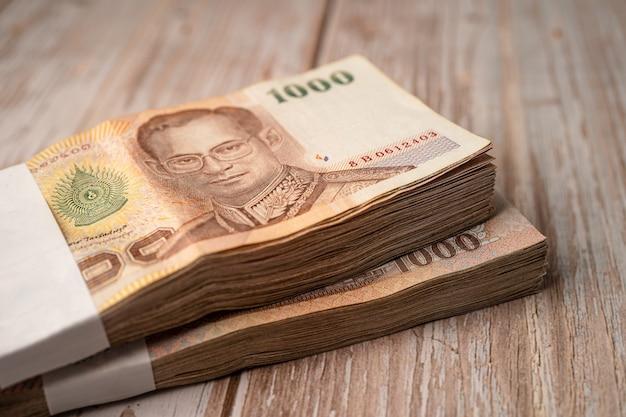 Pila de billetes de baht tailandés en mesa de madera