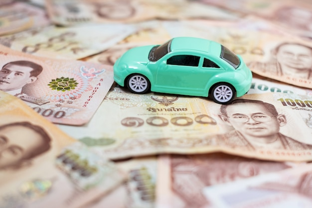 Pila de billetes con coche y calculadora.