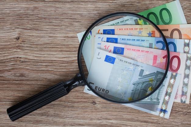 Pila de billetes en euros con lupa