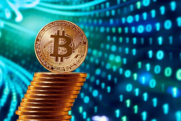 Pila de bitcoins dorados con un bitcoin en su borde colocado