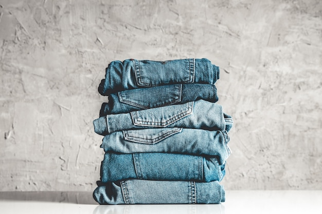 Pila de blue jeans sobre un fondo gris