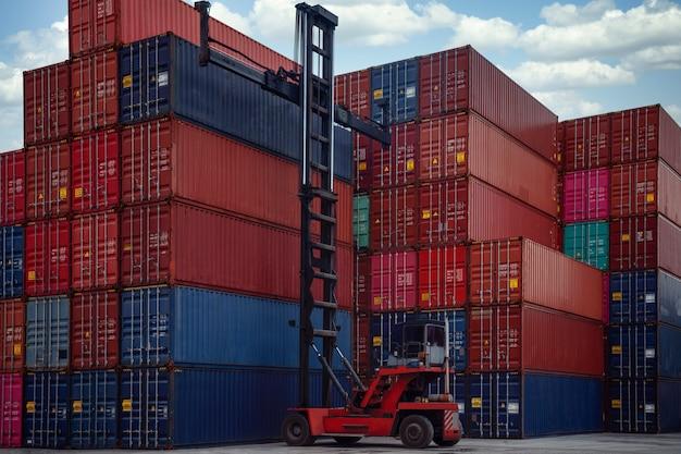 Pila de caja de contenedores en el puerto de transporte con carro elevador de contenedores, esta imagen se puede usar para el envío, el contenedor, la entrega y el concepto comercial