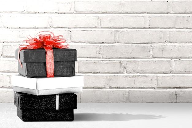 Pila de la caja de regalo sobre la mesa con una pared