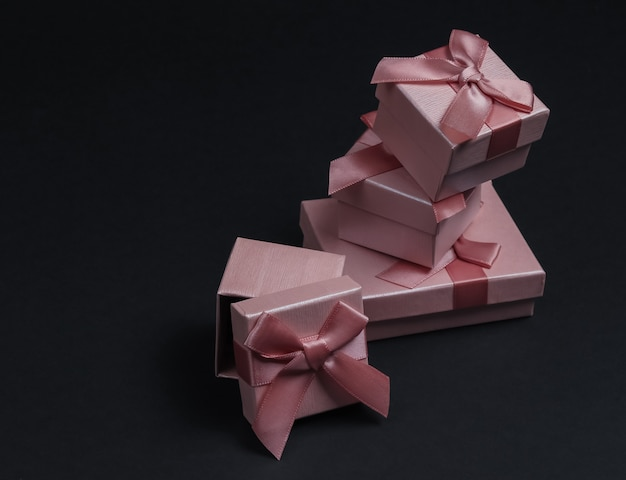 Pila de cajas de regalo con arcos sobre fondo negro de estudio. composición para navidad, cumpleaños o boda.