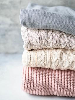 Pila de cálidos suéteres de lana tejida en tonos pastel contra la pared gris.