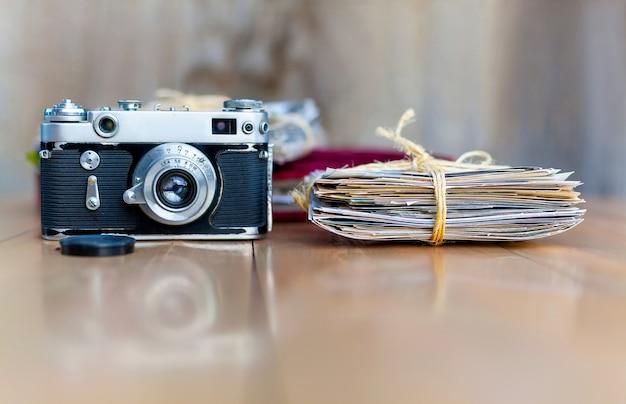 Pila de cámara vieja de fotos y álbum de fotos en una mesa de madera.