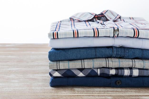 Pila de camisas de los hombres en la mesa de madera