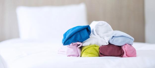 Pila de camiseta colorida en la cama en hotel de lujo o resort u hogar. relax, ropa de verano, lavandería y conceptos de vacaciones.