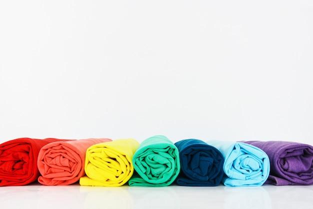 Pila de camiseta colorida enrollada sobre fondo blanco.