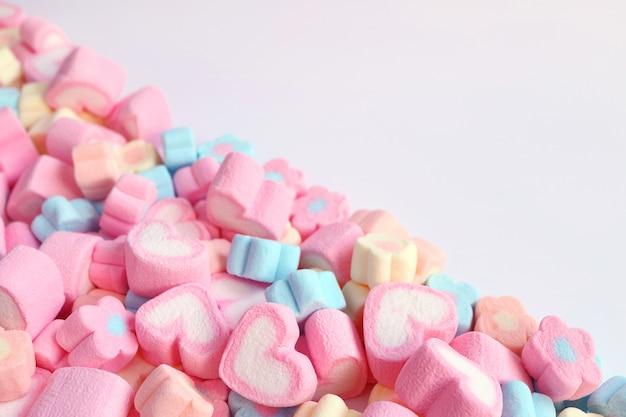 Pila de caramelos de malvavisco en forma de corazón en forma de corazón rosa y en forma de pastel con espacio libre para el diseño