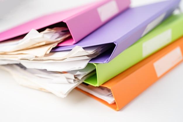 Pila de carpetas de archivos de varios colores sobre la mesa en la oficina.