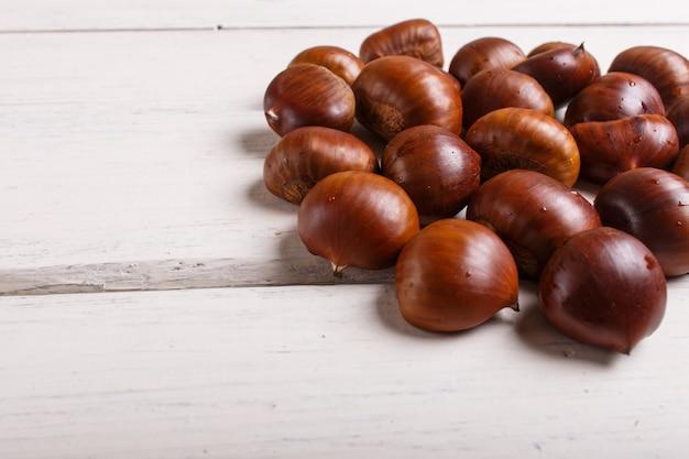 Pila de castañas dulces en el fondo de madera blanco