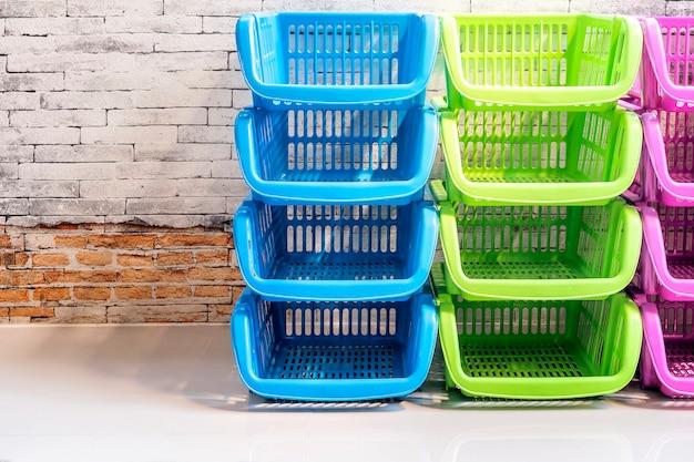 Pila de cesta plástica colorida con pared de ladrillo viejo, espacio de copia
