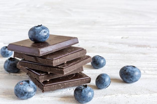 Pila de chocolate negro con arándanos maduros frescos