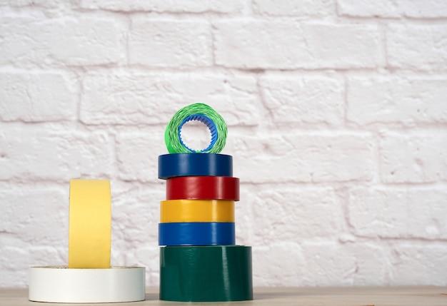 Pila de cinta aislante de colores sobre fondo de pared de ladrillo blanco