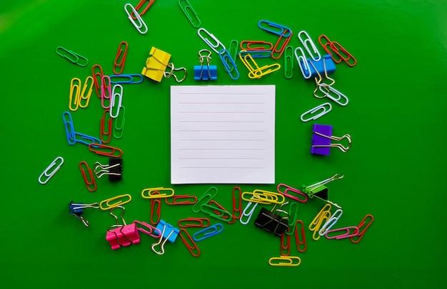 Pila de clips de papel aislado sobre fondo verde, documentos, concepto de suministros de oficina, escritorio de oficina sucio. lugar vacío para escritura y texto. vista superior, diseño. endecha plana.