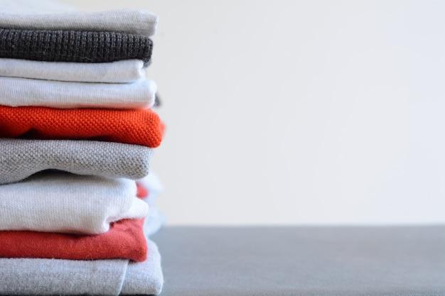 Pila de coloridas camisas dobladas en la mesa gris
